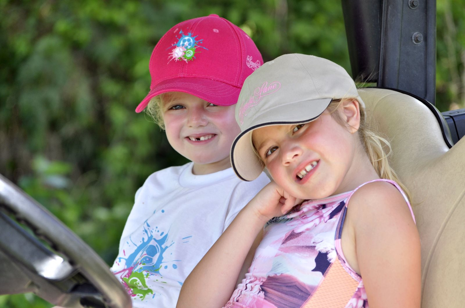 Two kids sitting in golf cart